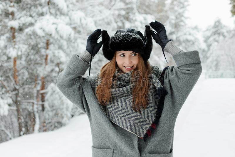 Belle position de jeune femme parmi les arbres neigeux dans la forêt d'hiver et la neige de apprécier images stock