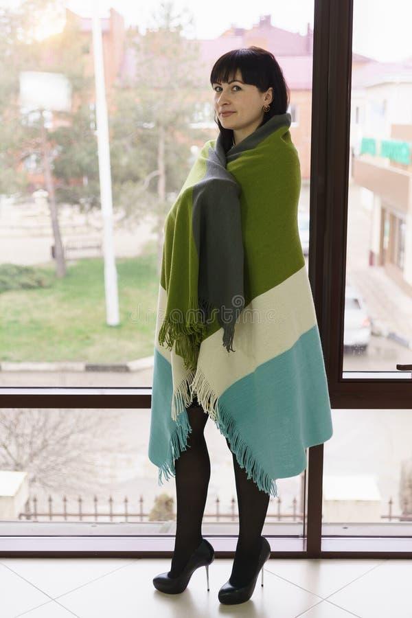 Belle position de trente ans de femme à la fenêtre, enveloppée dans une couverture tricolore attente image stock