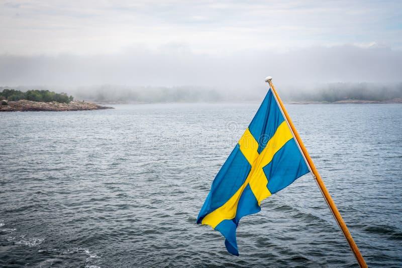 Belle position nordique d'été d'archipel de terre et d'île contre la mer et horizon flou avec le drapeau suédois dans le premier  photographie stock libre de droits