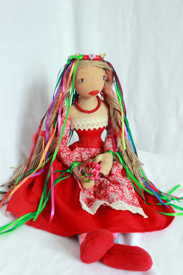 Belle poupée dans la robe rouge avec les rubans colorés image stock