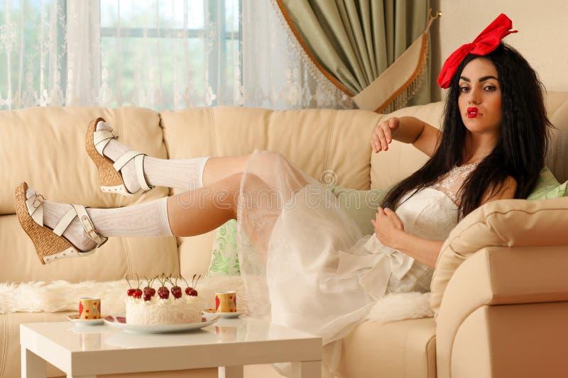 Belle poupée de femme dans une robe blanche se trouvant sur le sofa photos stock