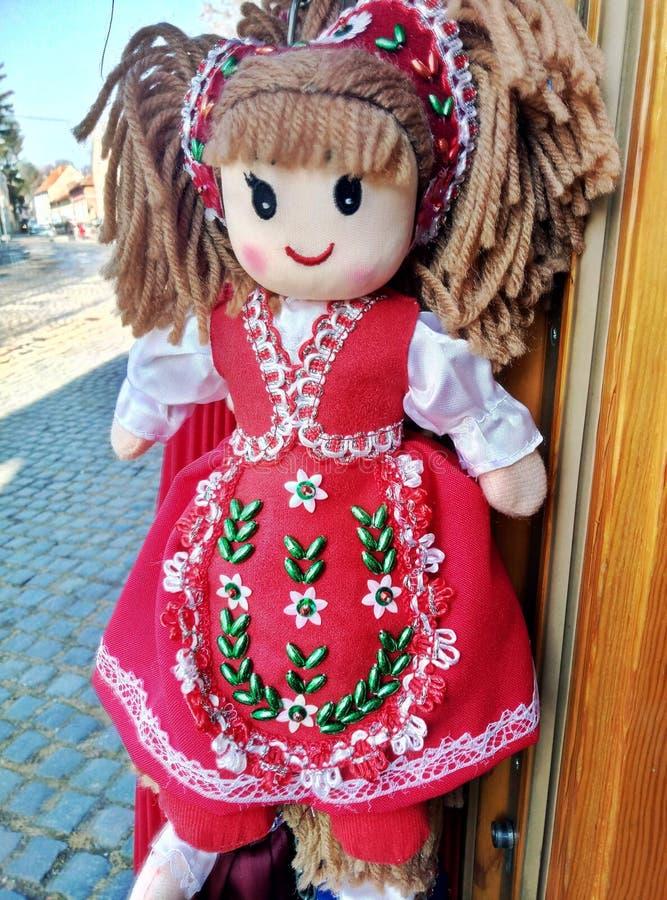 Belle poupée de tissu dans la robe traditionnelle rouge avec des fleurs image stock