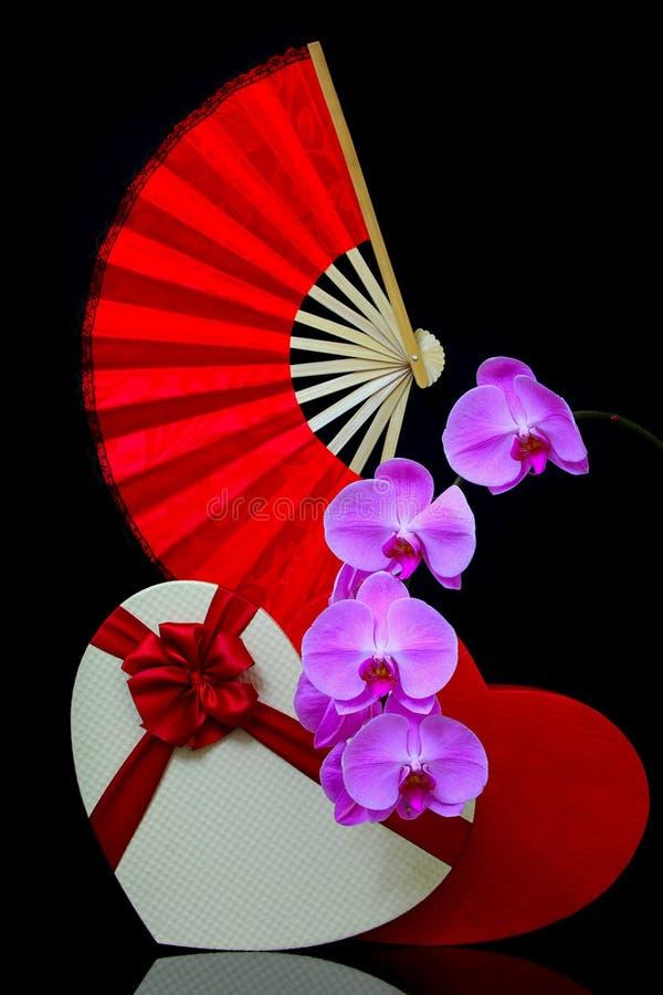 Belle présentation de vie morte avec ventilateur rouge pliant, boîte cadeau en forme de coeur et fleurs d'orchidées roses photographie stock