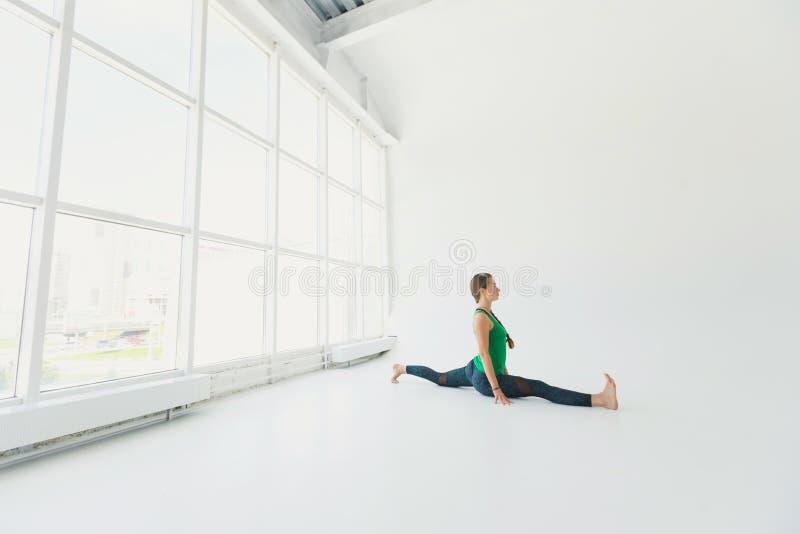 Belle pratique en matière de femme de yoga à un grand arrière-plan de hall de fenêtre Concept de yoga photographie stock