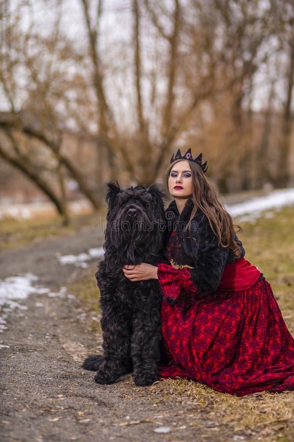 Belle princesse dans la robe rouge et la veste noire de fourrure posant dans la couronne avec son chien en Forest During Early Sp photographie stock