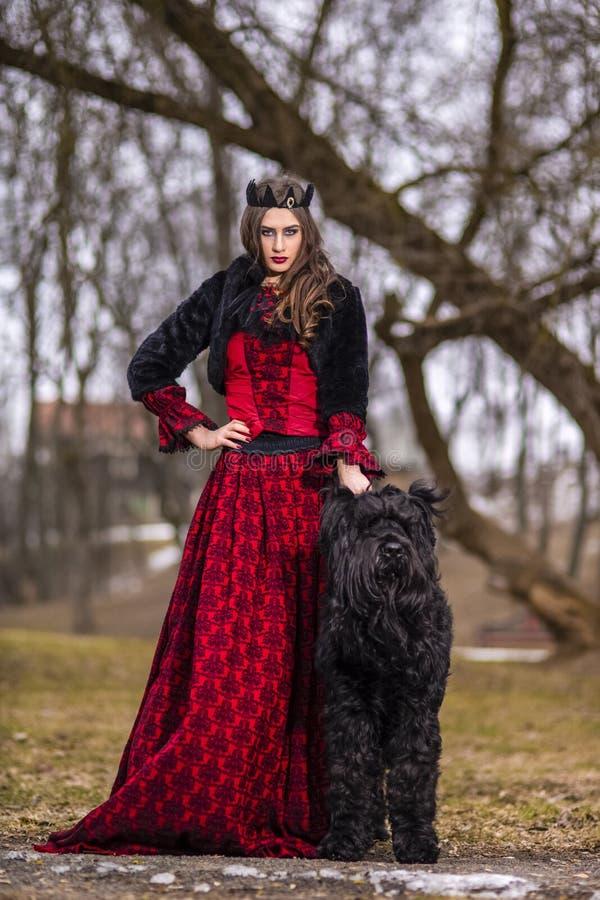 Belle princesse dans la robe rouge et la veste noire de fourrure posant dans la couronne avec son chien en Forest During Early Sp images stock
