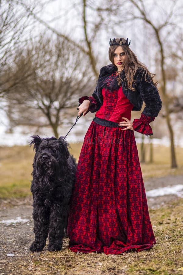 Belle princesse dans la robe rouge et la veste noire de fourrure posant dans la couronne avec son chien en Forest During Early Sp photo libre de droits