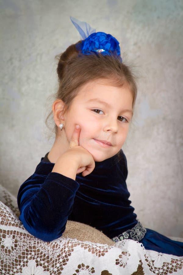 Belle princesse de petite fille dans la robe bleue se reposant sur la chaise blanche photographie stock libre de droits