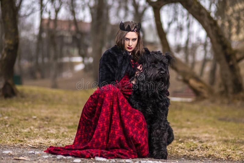 Belle princesse en robe rouge et fourrure noire avec la couronne et son chien en Forest During Early Spring Photographie d'art image stock