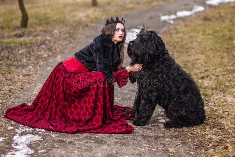 Belle princesse en robe rouge et fourrure noire avec la couronne et son chien en Forest During Early Spring Photographie d'art image libre de droits
