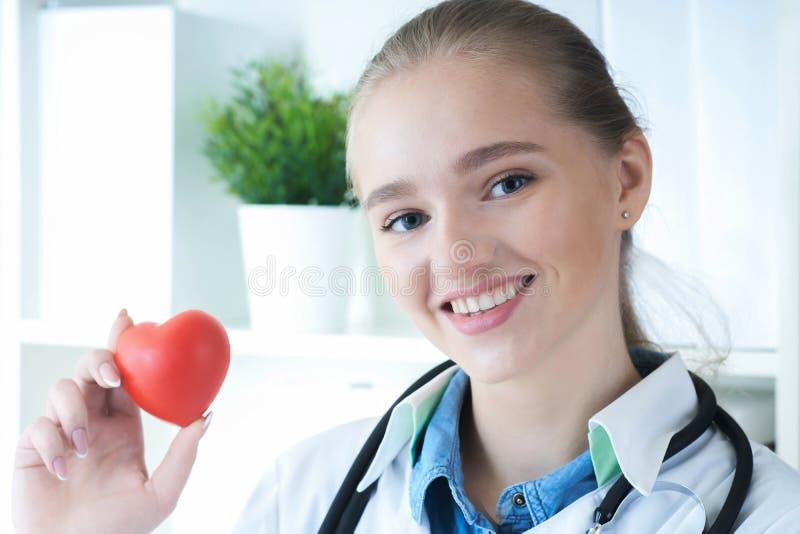 Belle prise femelle de sourire caucasienne de docteur en plan rapproch? rouge de coeur de jouet de bras Cardio- CPR d'?ducation d photos libres de droits