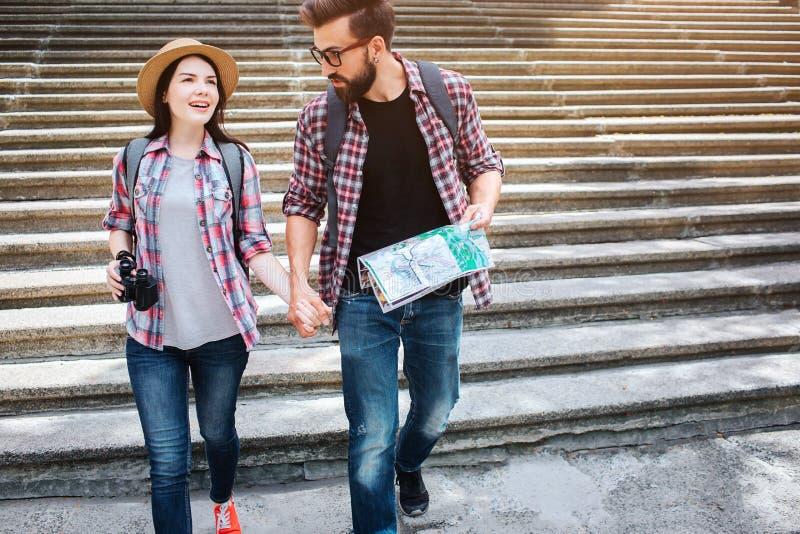 Belle promenade de couples ensemble Ils se tiennent main du ` s Regard de jeune homme à la femme Il tient la carte Ils marchent s images libres de droits