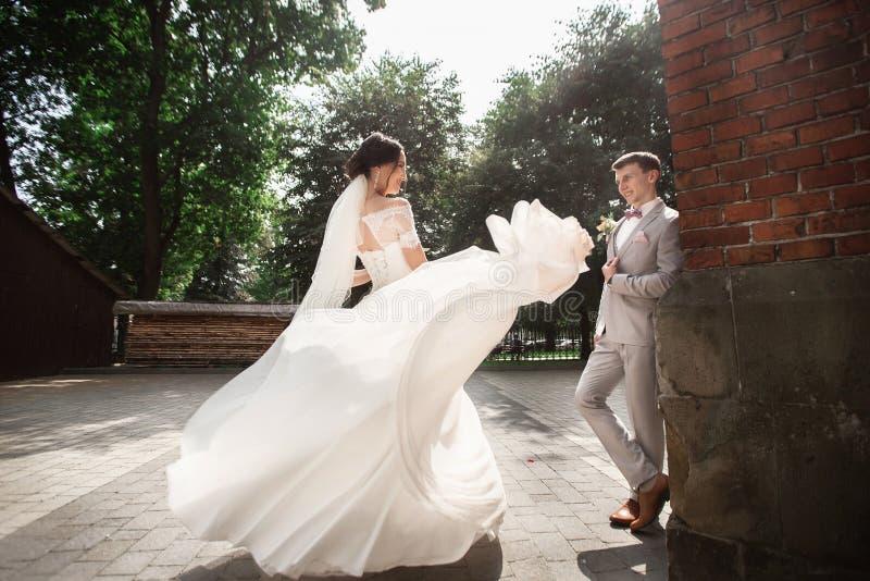 Belle promenade de couples de nouveaux mari?s pr?s de vieille ?glise chr?tienne photographie stock libre de droits