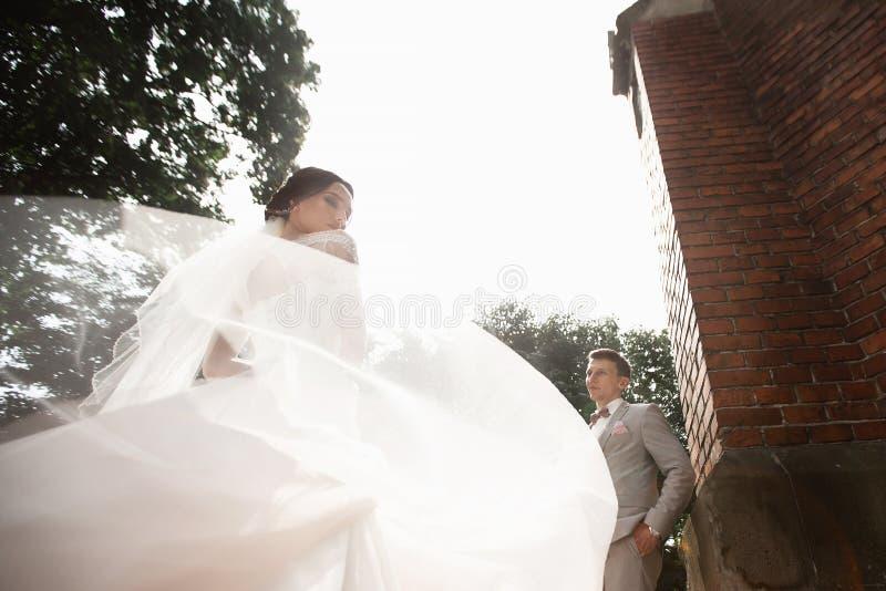 Belle promenade de couples de nouveaux mari?s pr?s de vieille ?glise chr?tienne photos libres de droits