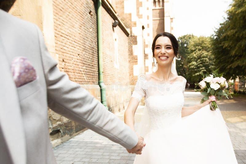 Belle promenade de couples de nouveaux mari?s pr?s de vieille ?glise chr?tienne image stock