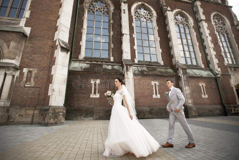 Belle promenade de couples de nouveaux mari?s pr?s de vieille ?glise chr?tienne photo stock