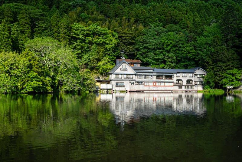 Belle réflexion verte naturelle abondante d'usine de montagne sur le lac frais Kinrin avec des bâtiments pendant le printemps image libre de droits