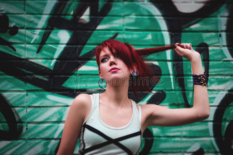 Belle ragazza e parete di graffity fotografia stock libera da diritti