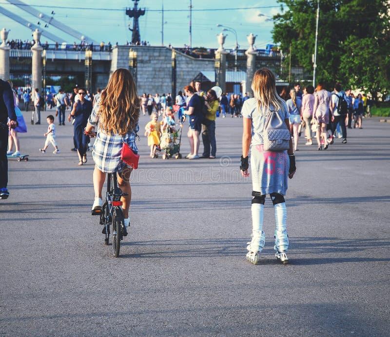Belle ragazze alla moda sui rulli e su una bicicletta fotografia stock