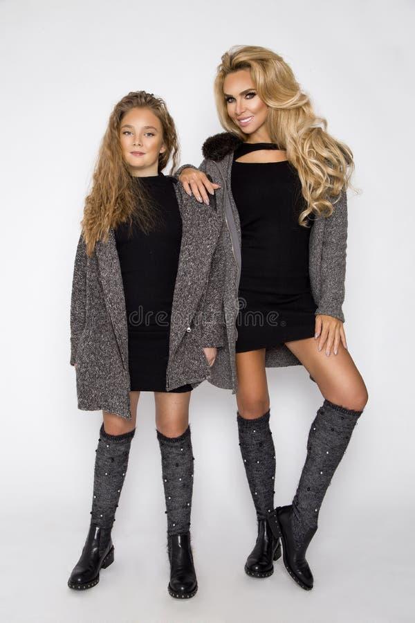 Belle ragazze bionde, madre con la figlia in abbigliamento di autunno-inverno su un fondo bianco nello studio fotografia stock