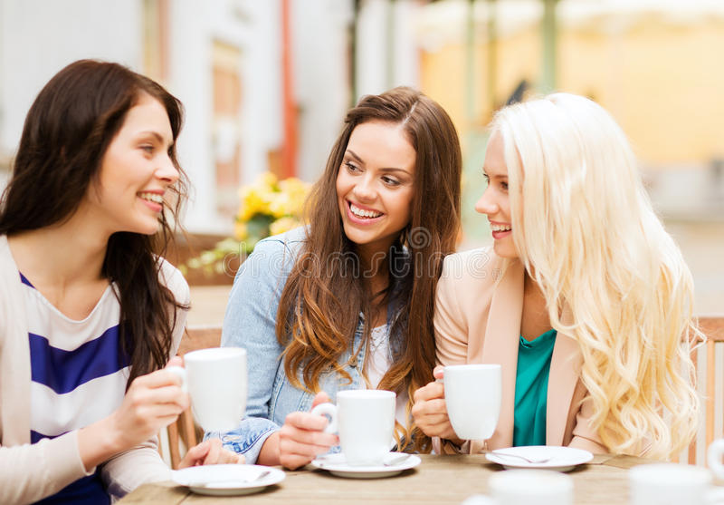 Belle ragazze che bevono caffè in caffè immagine stock libera da diritti
