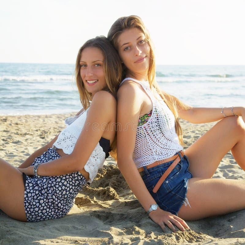 Belle ragazze con capelli lunghi che si siedono sulla spiaggia al tramonto che sorridono guardando macchina fotografica immagine stock libera da diritti