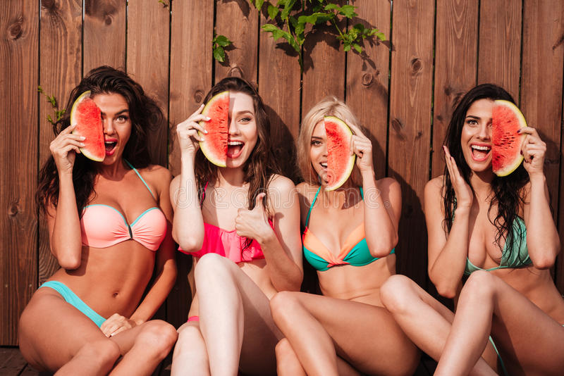 Belle ragazze felici in bikini che mangiano anguria allo stagno immagini stock libere da diritti