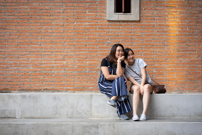 Belle ragazze moderne vicino al muro di mattoni arancio Pantaloni a vita bassa della gioventù immagini stock libere da diritti