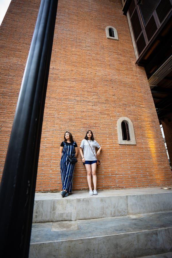 Belle ragazze moderne vicino al muro di mattoni arancio Pantaloni a vita bassa della gioventù fotografia stock libera da diritti