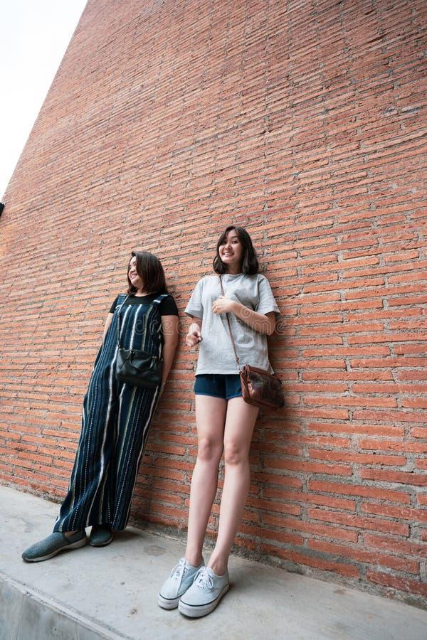 Belle ragazze moderne vicino al muro di mattoni arancio Pantaloni a vita bassa della gioventù fotografie stock libere da diritti