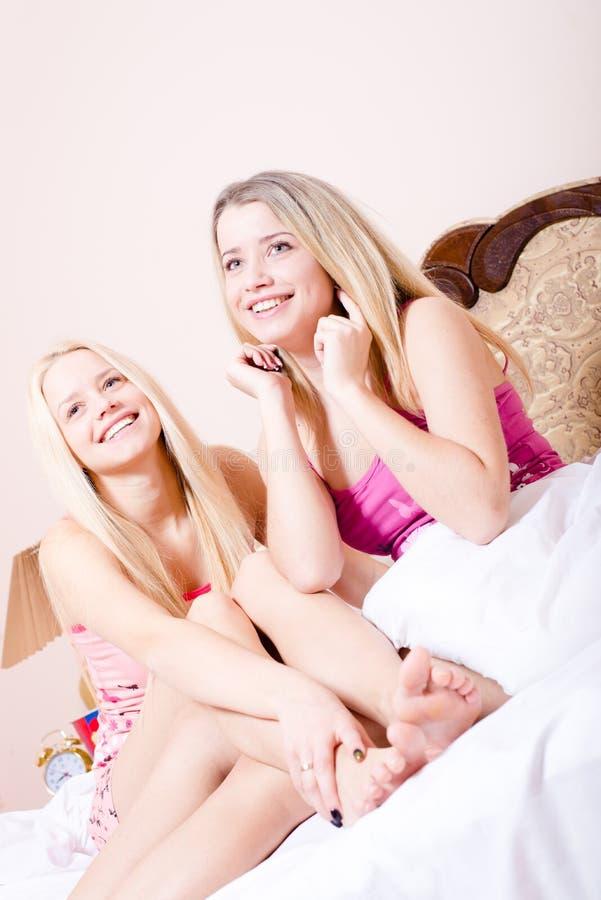 2 belle ragazze o giovani donne bionde abbastanza sveglie delle sorelle in pigiami che si siedono sul letto bianco divertendosi s immagine stock