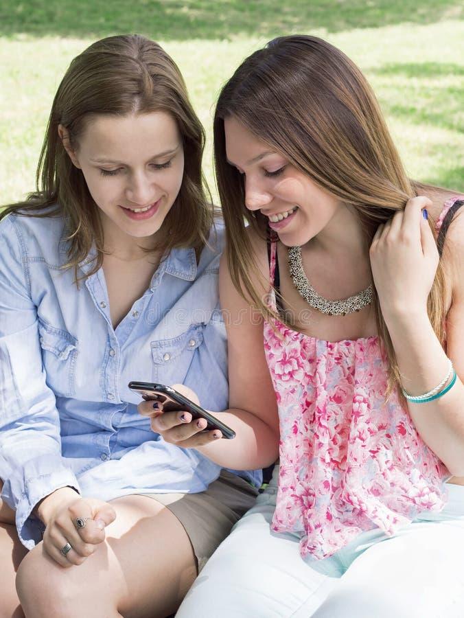 Belle ragazze sorridenti con il telefono cellulare immagini stock