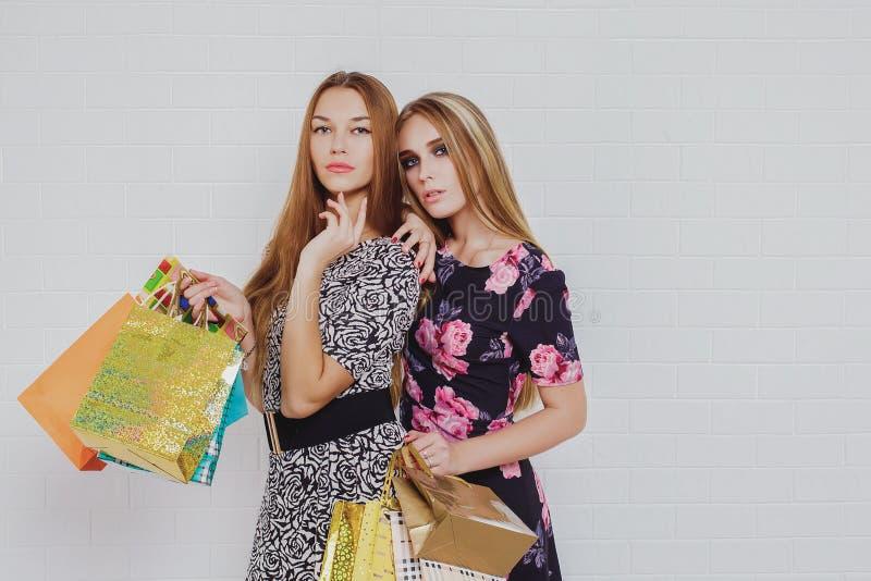 Belle ragazze teenager che portano i sacchetti della spesa, sopra fondo bianco Colpo dello studio immagini stock