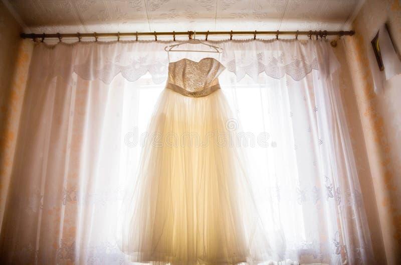 Belle robe de mariage accrochant dans la salle du ` s de jeune mariée photos stock