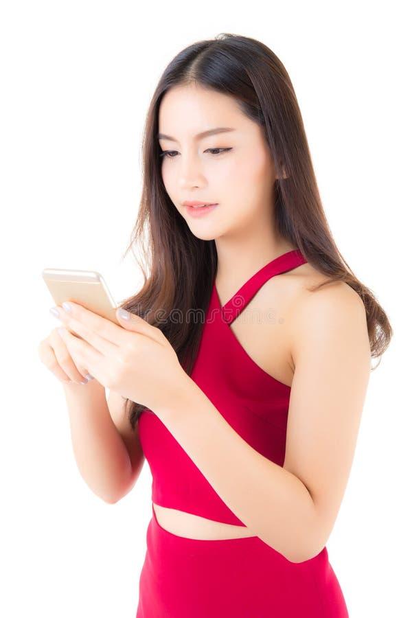 Belle robe rouge asiatique d'usage de jeune femme utilisant un téléphone portable photos stock