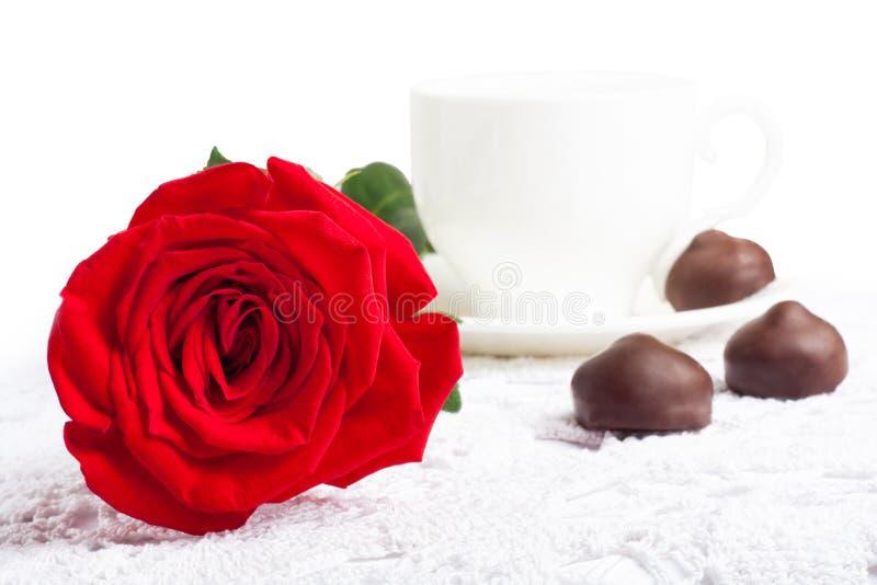 Belle rosa rossa e tazza di tè caldo con cioccolato fotografia stock