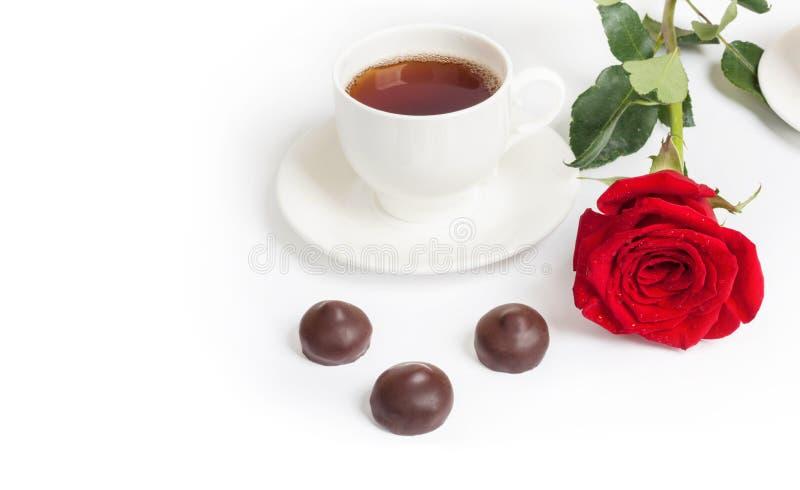 Belle rosa rossa e tazza di tè caldo con cioccolato fotografie stock