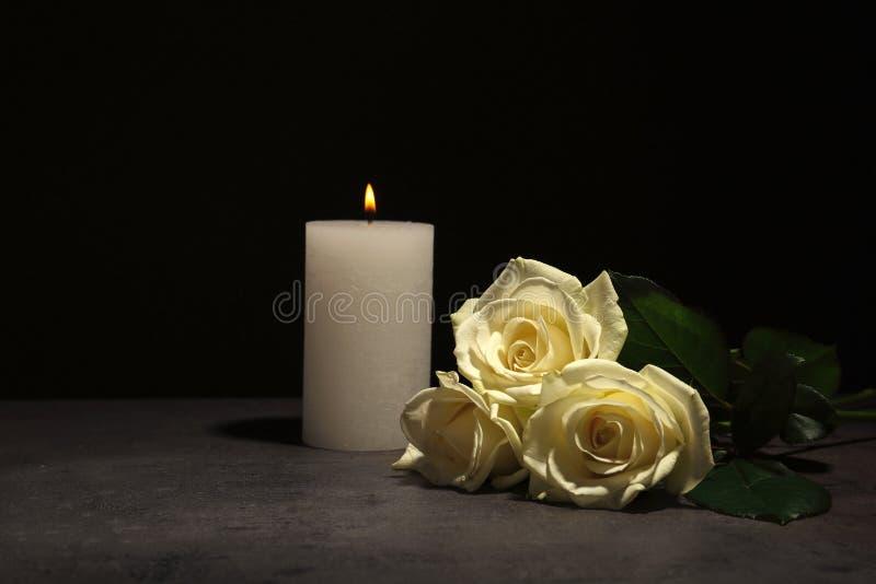 Belle rose bianche e candela sulla tavola fotografie stock
