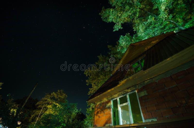 Belle rue de village de paysage avec des bâtiments et des arbres et grande pleine lune au ciel nocturne Grand Caucase photo stock