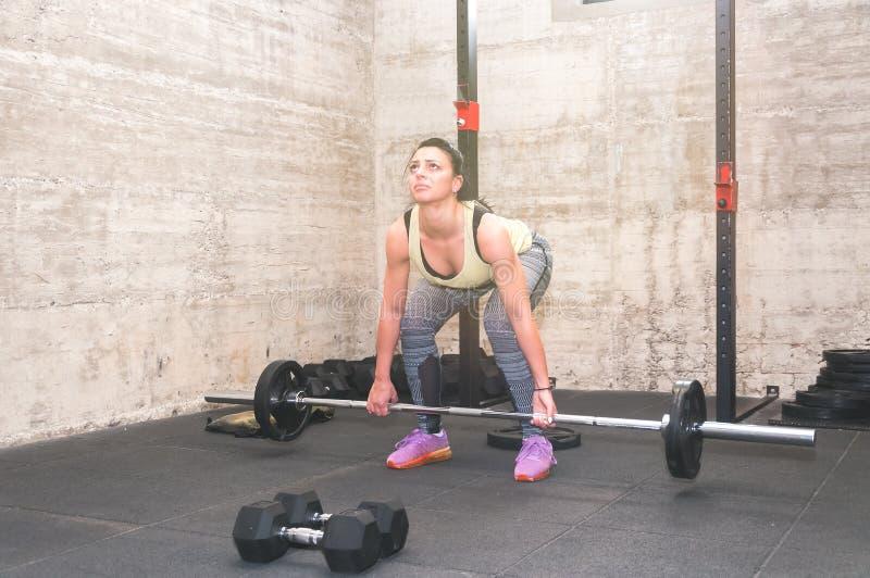 Belle séance d'entraînement morte d'ascenseur de jeune et attirante fille dans le gymnase avec de petits poids de barbell comme v photo libre de droits