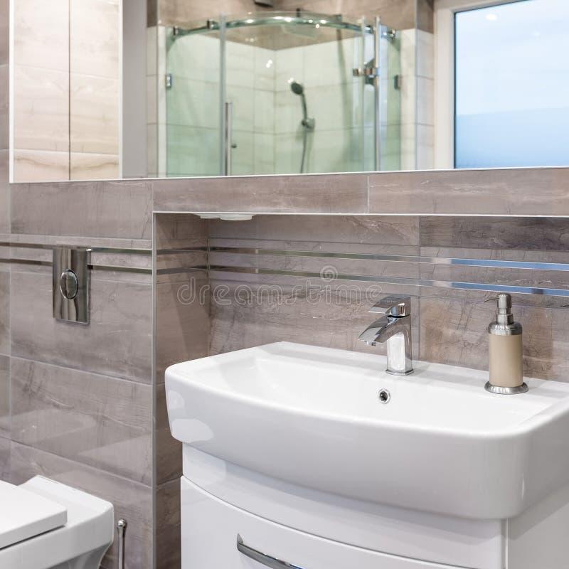 Belle salle de bains de villa dans le beige photo stock