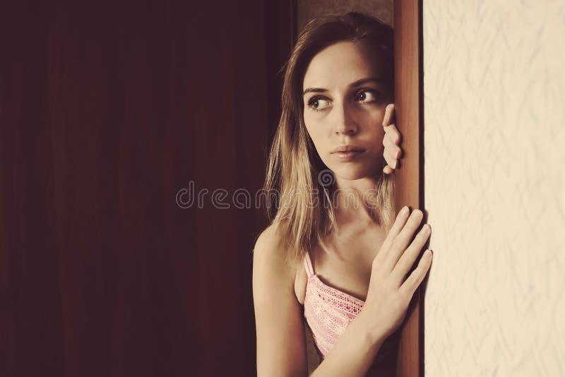 Belle sbirciate della ragazza che danno una occhiata dalla entrata fotografie stock libere da diritti