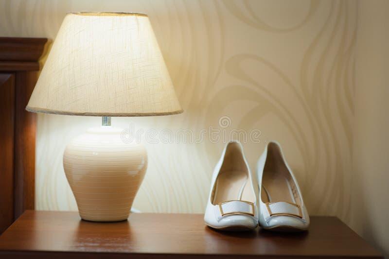 Belle scarpe bianche dalla sposa con una lampada fotografia stock