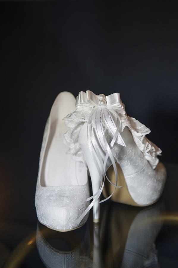 Belle scarpe eleganti della sposa su un fondo nero fotografia stock libera da diritti