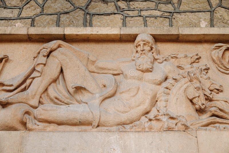 Belle sculpture antique en bas-relief sur le style du grec ancien de mur Dieu Poseidon, donateur des personnes arrosent image libre de droits