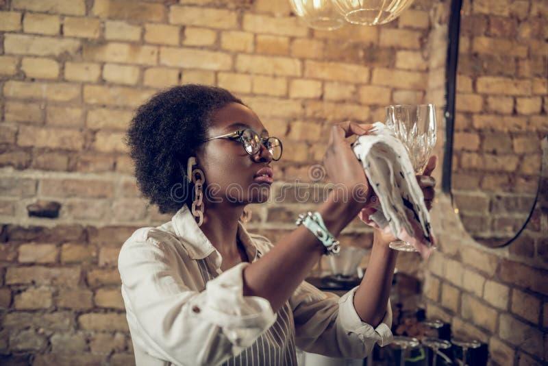 Belle serveuse afro-américaine intéressée aux cheveux foncés gentil-agréable faisant le polissage en verre de vin image libre de droits
