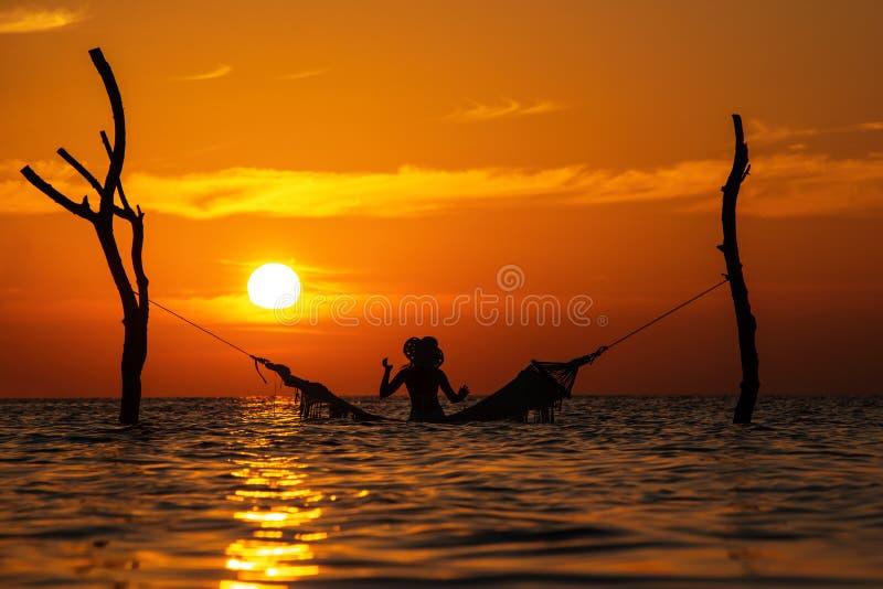 Belle silhouette de jeune femme avec l'oscillation posant en mer sur le coucher du soleil, paysage romantique maldivien photos libres de droits