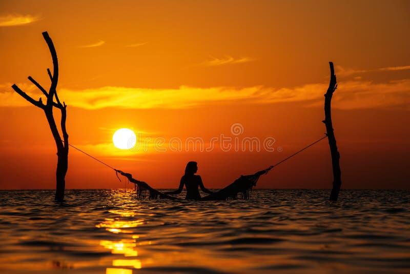 Belle silhouette de jeune femme avec l'oscillation posant en mer sur le coucher du soleil, paysage romantique maldivien photographie stock