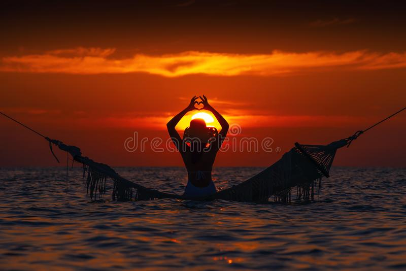 Belle silhouette de jeune femme avec l'oscillation posant en mer sur le coucher du soleil, paysage romantique maldivien images libres de droits