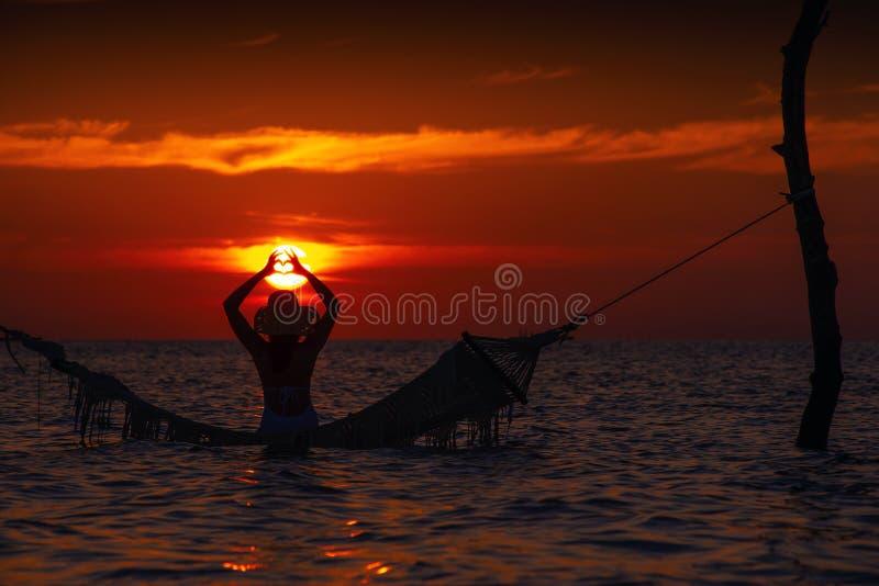 Belle silhouette de jeune femme avec l'oscillation posant en mer sur le coucher du soleil, paysage romantique maldivien images stock